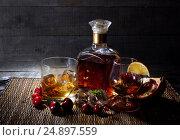 Бутылка коньяка,виски на деревянном фоне с двумя бокалами,фруктами и льдом. Стоковое фото, фотограф Беляева Юлия / Фотобанк Лори