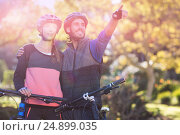 Купить «Biker couple with mountain bike pointing in distance», фото № 24899035, снято 26 марта 2019 г. (c) Wavebreak Media / Фотобанк Лори