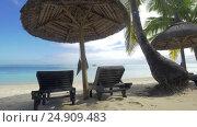 View of empty chaise-longue near native sun umbrella and palm trees against blue water, Mauritius Island. Стоковое видео, видеограф Данил Руденко / Фотобанк Лори