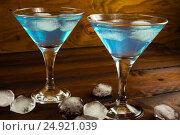 Купить «Two blue cocktails in glasses on dark wooden background», фото № 24921039, снято 15 марта 2016 г. (c) TasiPas / Фотобанк Лори
