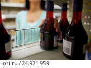Купить «hand taking bottle of vinegar from shelf at shop», фото № 24921959, снято 2 ноября 2016 г. (c) Syda Productions / Фотобанк Лори