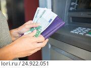 Купить «close up of hand withdrawing money at atm machine», фото № 24922051, снято 8 сентября 2016 г. (c) Syda Productions / Фотобанк Лори