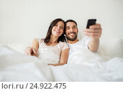 happy couple lying in bed at home and watching tv, фото № 24922475, снято 2 сентября 2016 г. (c) Syda Productions / Фотобанк Лори