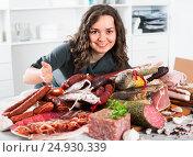 Купить «Woman costs near table on which sausages and smoked meat», фото № 24930339, снято 17 августа 2018 г. (c) Яков Филимонов / Фотобанк Лори