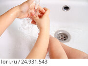 Купить «Children washing hands in a white sink under running water», фото № 24931543, снято 31 декабря 2015 г. (c) Александр Волков / Фотобанк Лори