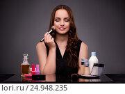 Купить «Woman doing makeup on dark background», фото № 24948235, снято 7 сентября 2016 г. (c) Elnur / Фотобанк Лори