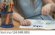 Купить «Little girl draws images in notebook using pencils», видеоролик № 24948883, снято 15 декабря 2016 г. (c) worker / Фотобанк Лори
