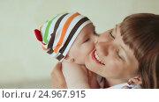 Купить «Baby tenderly kisses his mother. Dressed baby in striped shorts and cap», видеоролик № 24967915, снято 20 января 2017 г. (c) Mikhail Davidovich / Фотобанк Лори
