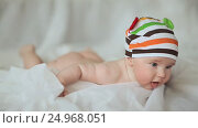 Купить «Funny four month old baby lying on his stomach and smiling», видеоролик № 24968051, снято 20 января 2017 г. (c) Mikhail Davidovich / Фотобанк Лори