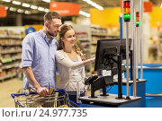 Купить «couple buying food at grocery at cash register», фото № 24977735, снято 21 октября 2016 г. (c) Syda Productions / Фотобанк Лори
