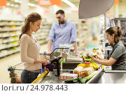 Купить «woman buying food at grocery store cash register», фото № 24978443, снято 21 октября 2016 г. (c) Syda Productions / Фотобанк Лори