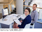 Купить «Businesswoman working at desk with colleague», фото № 24980251, снято 3 ноября 2016 г. (c) Wavebreak Media / Фотобанк Лори