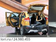 Купить «Новинки АвтоВАЗ — Лада Икс Рэй Кросс Концепт золотистого цвета с открытыми дверьми и девушкой в багажнике на Московском автосалоне, вид сзади слева. Lada X Ray Cross Concept at the Moscow motor show», фото № 24980455, снято 31 августа 2016 г. (c) Илья Илмарин / Фотобанк Лори