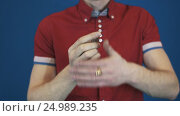 Close up illusionist in red shirt perform magic trick disappear in hands coin. Стоковое видео, видеограф Александр Багно / Фотобанк Лори