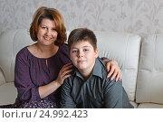 Купить «Mother and son sitting on a sofa in room», фото № 24992423, снято 22 января 2017 г. (c) Володина Ольга / Фотобанк Лори
