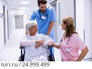 Купить «Male and female doctor interacting with female senior patient on wheelchair in corridor», фото № 24999499, снято 6 ноября 2016 г. (c) Wavebreak Media / Фотобанк Лори