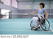 Купить «Disabled mature woman on wheelchair playing tennis on tennis court», фото № 25002627, снято 6 января 2017 г. (c) Andrejs Pidjass / Фотобанк Лори