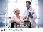 Купить «Physiotherapist assisting senior patient with hand exercise», фото № 25004607, снято 17 июля 2018 г. (c) Wavebreak Media / Фотобанк Лори