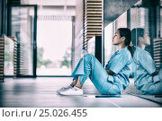 Купить «Side view of nurse sitting on floor», фото № 25026455, снято 17 июня 2019 г. (c) Wavebreak Media / Фотобанк Лори