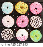 Купить «Set of colorful donuts on black wooden background», фото № 25027943, снято 27 января 2017 г. (c) Наталия Пыжова / Фотобанк Лори