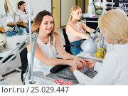 Купить «Two women clients having manicure done in nail salon», фото № 25029447, снято 2 ноября 2016 г. (c) Яков Филимонов / Фотобанк Лори
