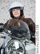 Купить «Женщина мотоциклист в шлеме сидит за рулем, ветровое стекло и фара мотоцикла», фото № 25035139, снято 28 января 2017 г. (c) Кекяляйнен Андрей / Фотобанк Лори