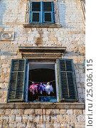 Купить «Два окна со ставнями и тремя куклами на верёвочке в средневековом здании с гербом. Дубровник, Хорватия.», фото № 25036115, снято 25 августа 2016 г. (c) Устенко Владимир Александрович / Фотобанк Лори