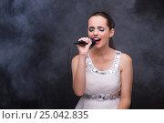 Купить «Young girl singing in karaoke club», фото № 25042835, снято 25 августа 2016 г. (c) Elnur / Фотобанк Лори