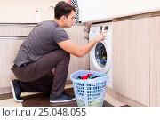 Купить «Young husband man doing laundry at home», фото № 25048055, снято 10 октября 2016 г. (c) Elnur / Фотобанк Лори