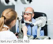 Купить «Female optician doing eye examination with aid of slit lamp», фото № 25056163, снято 20 июля 2018 г. (c) Яков Филимонов / Фотобанк Лори