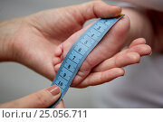 Купить «close up of hands with tape measuring baby foot», фото № 25056711, снято 23 ноября 2016 г. (c) Syda Productions / Фотобанк Лори