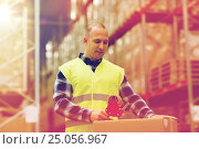 Купить «man in safety vest packing box at warehouse», фото № 25056967, снято 9 декабря 2015 г. (c) Syda Productions / Фотобанк Лори
