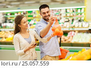 Купить «couple with smartphone buying oranges at grocery», фото № 25057559, снято 21 октября 2016 г. (c) Syda Productions / Фотобанк Лори