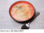Купить «Тарелка супа и ложка на деревянном столе», эксклюзивное фото № 25063891, снято 2 февраля 2017 г. (c) Яна Королёва / Фотобанк Лори