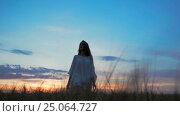 Купить «Young girl in a field at sunset», видеоролик № 25064727, снято 6 декабря 2016 г. (c) Raev Denis / Фотобанк Лори