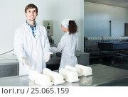 Купить «Portrait of man and woman dressed in lab coats are looking happy on the factory», фото № 25065159, снято 26 марта 2019 г. (c) Яков Филимонов / Фотобанк Лори