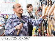 Купить «Ordinary cheerful smiling customer and friendly seller choosing hammer», фото № 25067567, снято 18 ноября 2018 г. (c) Яков Филимонов / Фотобанк Лори