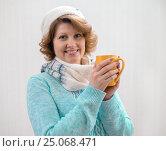 Купить «woman in sweater, hat and scarf holding yellow cup of tea», фото № 25068471, снято 29 октября 2015 г. (c) Володина Ольга / Фотобанк Лори