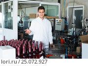 Купить «friendly man employee standing in final section of wine production on factory», фото № 25072927, снято 21 сентября 2016 г. (c) Яков Филимонов / Фотобанк Лори