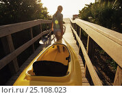 Купить «Woman taking her kayak and oar along the boardwalk at Vero Beach, Florida, usa 2003. Model Released.», фото № 25108023, снято 26 апреля 2018 г. (c) Nature Picture Library / Фотобанк Лори