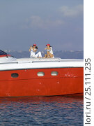 """Купить «Two women sitting on the foredeck of high performance motoryacht """"Azzurra 63'"""", as it cruises off Procida Island, Italy. The luxury yacht was...», фото № 25111235, снято 19 января 2020 г. (c) Nature Picture Library / Фотобанк Лори"""