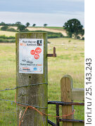 Купить «Farmers Guardian notice on field gatepost warning walkers that dogs can kill livestock, with sheep in distance. Norfolk, England UK. August.», фото № 25143243, снято 21 июля 2018 г. (c) Nature Picture Library / Фотобанк Лори
