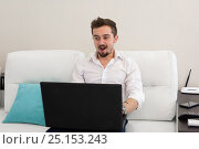 Man with laptop. Handsome businessman working with laptop in office. Happy young man in white shirt sitting on sofa at home, working on laptop computer, smiling. Стоковое фото, фотограф Довженко Анастасия / Фотобанк Лори