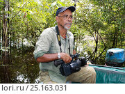 Photographer/ film-maker Steve O Taylor holding video camera, Gunung Palung National Park, West Kalimantan, Indonesian Borneo. July 2010. Стоковое фото, фотограф Steve O. Taylor (GHF) / Nature Picture Library / Фотобанк Лори