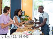 Купить «Woman entering pin code on credit card reader at counter», фото № 25169043, снято 12 октября 2016 г. (c) Wavebreak Media / Фотобанк Лори