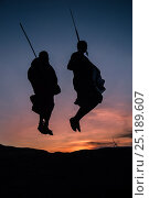 Купить «Two Masaai warriors silhouetted performing traditional jump / leap kopje at sunset. Ngorongoro Conservation Area / Serengeti National Park, Tanzania. March 2014.», фото № 25189607, снято 17 августа 2018 г. (c) Nature Picture Library / Фотобанк Лори