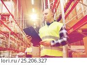 Купить «man with clipboard in safety vest at warehouse», фото № 25206327, снято 9 декабря 2015 г. (c) Syda Productions / Фотобанк Лори