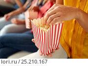 Купить «close up of happy friends eating popcorn at home», фото № 25210167, снято 14 августа 2016 г. (c) Syda Productions / Фотобанк Лори