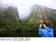 Купить «Woman taking photographs in remote, misty, Doubtful Sound. South Island, New Zealand. March 2009.», фото № 25228263, снято 19 июля 2018 г. (c) Nature Picture Library / Фотобанк Лори