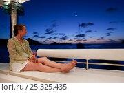 "Купить «Woman relaxing on board Privilege 745 catamaran ""Matau"" while cruising in the Grenadines, Caribbean, January 2010. Model and Property released.», фото № 25325435, снято 22 июля 2018 г. (c) Nature Picture Library / Фотобанк Лори"